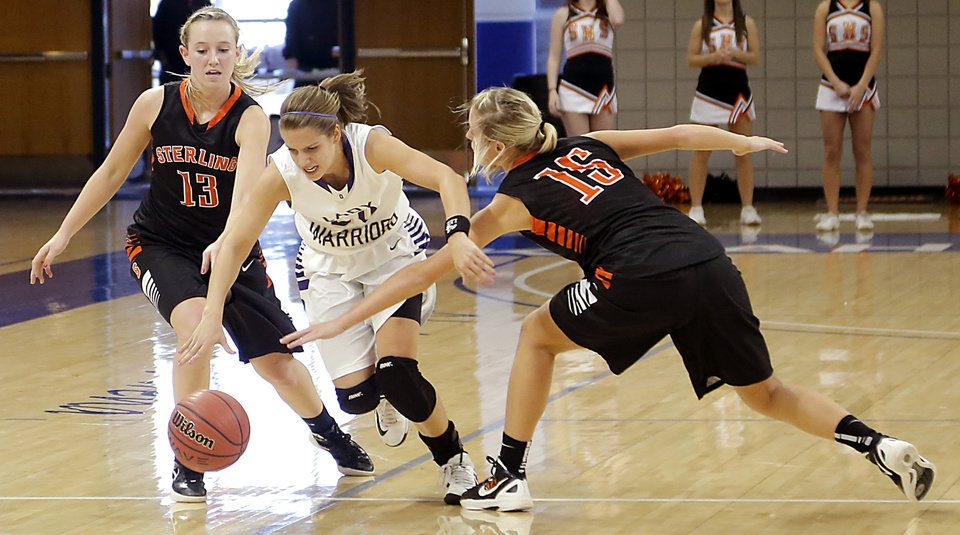 Photo - Okarche's Morgan Vogt (20) takes the ball between Sterling's Laurie Derrico (13) and Madison Bradshaw (15) during the Class A girls state quarterfinal game between Okarche and Sterling at Oklahoma City University on Thursday, Feb. 28, 2013, in Oklahoma City, Okla. Photo by Chris Landsberger, The Oklahoman