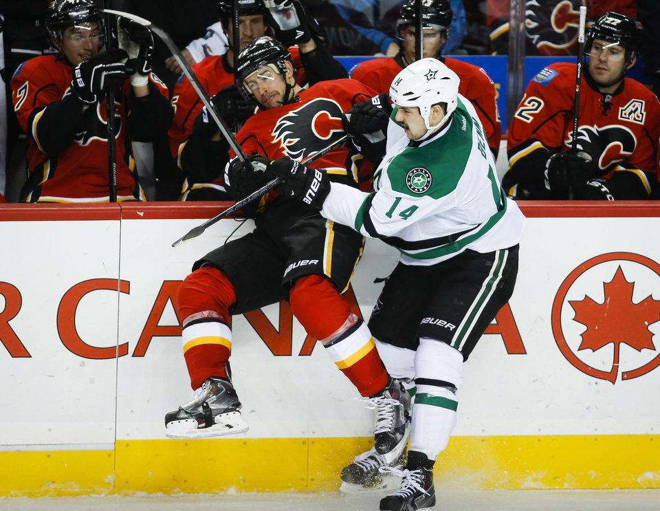 Photo - Dallas Stars' Jamie Benn, right, checks Calgary Flames' Chris Butler during the third period of an NHL hockey game in Calgary, Alberta, Thursday, Nov. 14, 2013. The Stars won 7-3. (AP Photo/The Canadian Press, Jeff McIntosh)