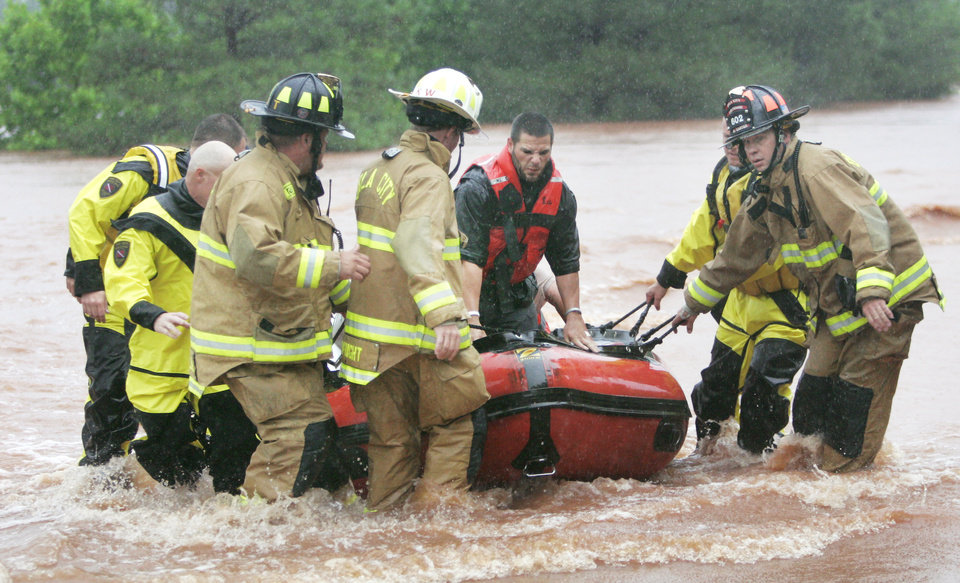 Photo - Firefighters rescue motorists from a bridge near Hefner Road and Sooner Road. Photos by Steve Gooch, The Oklahoman