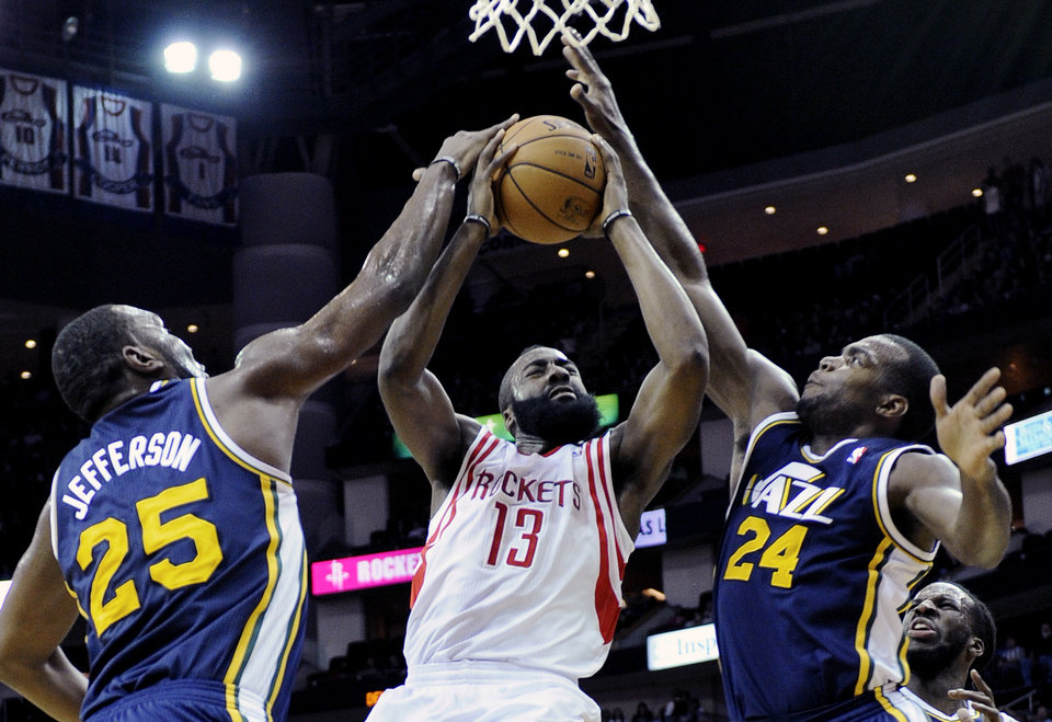Photo - Houston Rockets' James Harden (13) goes to the basket while double-teamed by Utah Jazz Al Jefferson (25) and Paul Millsap (24) in the first half of an NBA basketball game on Saturday, Dec. 1, 2012, in Houston. (AP Photo/Pat Sullivan)