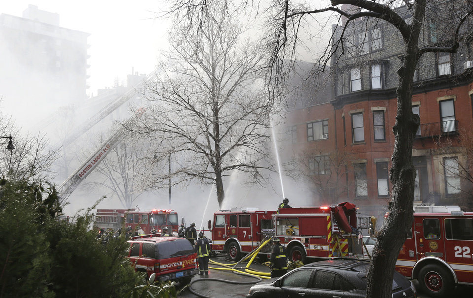 Photo - Fighters battle a multi-alarm fire at a four-story brownstone in the Back Bay neighborhood near the Charles River, Wednesday, March 26, 2014, in Boston.  A Boston city councilor said two firefighters have died in a fire that ripped through a brownstone. (AP Photo/Steven Senne)