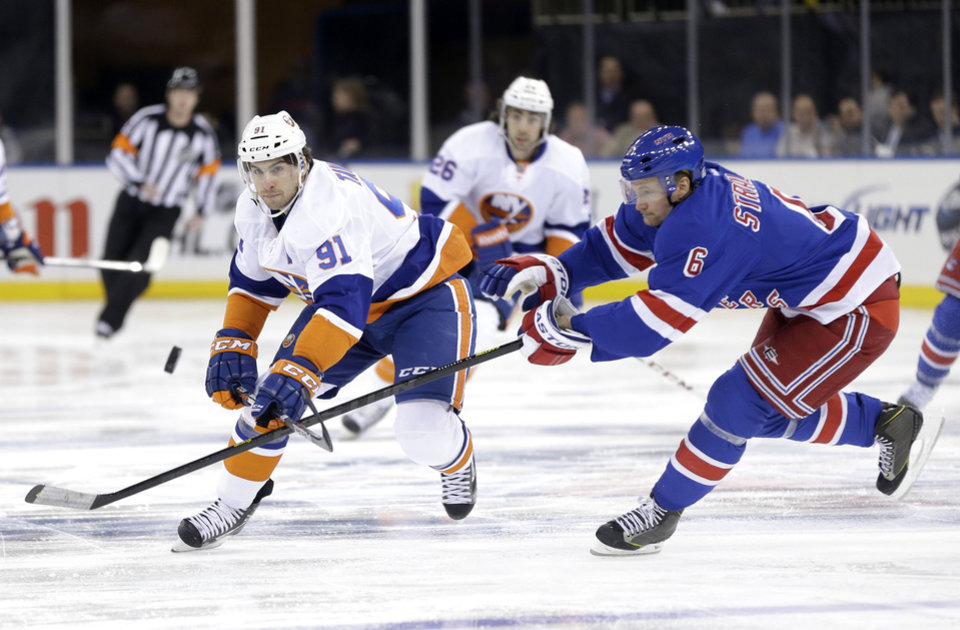 Photo - New York Rangers' Anton Stralman, right, tries to block a pass by New York Islanders' John Tavares during the first period of the NHL hockey game in New York, Thursday, Feb. 7, 2013.  (AP Photo/Seth Wenig)