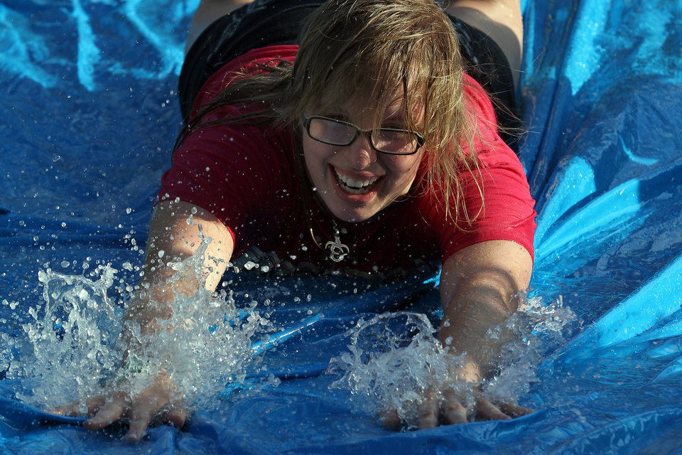 Alanna Grisham of Bartlesville slides on the slip and slide during the water wars at the move-in week activities at the University of Central Oklahoma in Edmond Sunday night, August 12th, 2012. PHOTO BY HUGH SCOTT, FOR THE OKLAHOMAN ORG XMIT: KOD