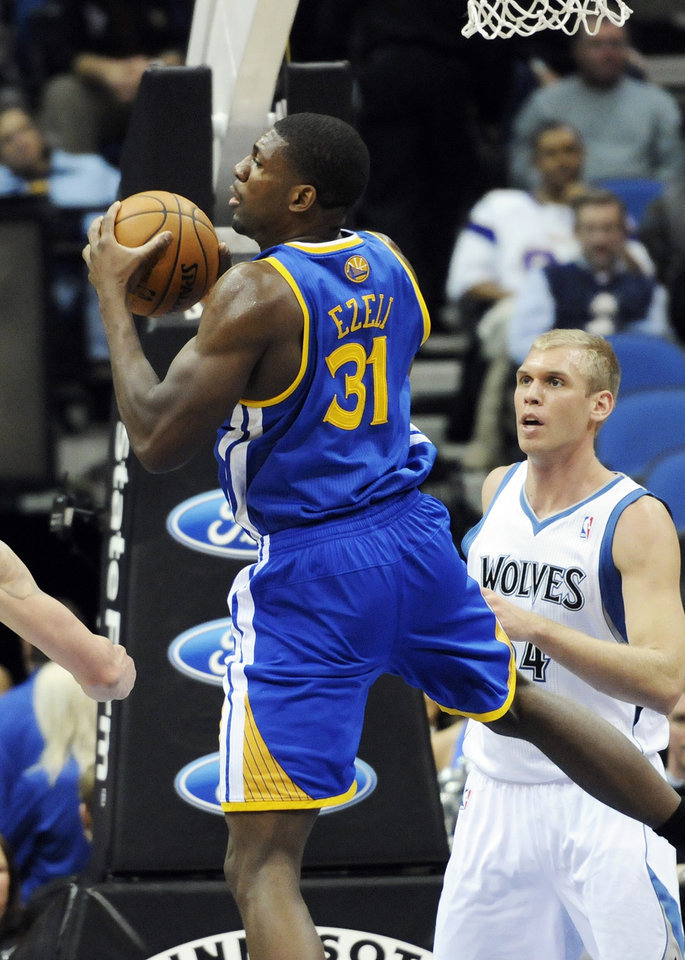 Minnesota Timberwolves' Greg Stiemsma, right, looks on as Golden State Warriors' Festus Ezeli, of Nigeria, pulls in a rebound in the first half of an NBA basketball game on Friday, Nov. 16, 2012, in Minneapolis. (AP Photo/Jim Mone)