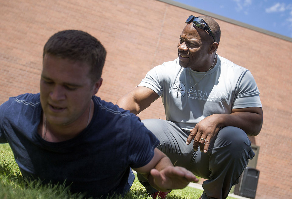 Photo -       Ron Williams, a nondenominational Christian pastor, right, assists Jeremy Ware through back muscle exercises with a group of Utah National Guard members at their headquarters on Thursday, Aug. 14, 2014. (Laura Seitz, Deseret News)