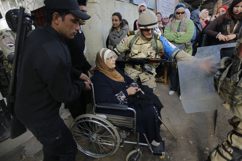 Photo - An Egyptian army soldier and policemen, left, help an elderly woman on a wheelchair in front of a polling station in Cairo, Egypt, Tuesday, Jan. 14, 2014. Egyptians are voting Tuesday on a draft for their country's new constitution that represents a key milestone in a military-backed roadmap put in place after President Mohammed Morsi was overthrown in a popularly backed coup last July. (AP Photo/Amr Nabil)