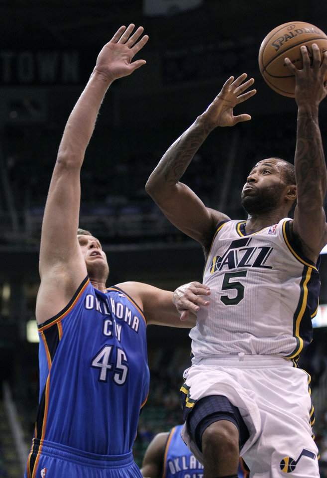Photo - Utah Jazz guard Mo Williams (5) drives to the basket as Oklahoma City Thunder center Cole Aldrich (45) defends in the third quarter during an preseason NBA basketball game on Friday, Oct. 12, 2012, in Salt Lake City. The Jazz defeated the Thunder 97-81. (AP Photo/Rick Bowmer) ORG XMIT: UTRB111
