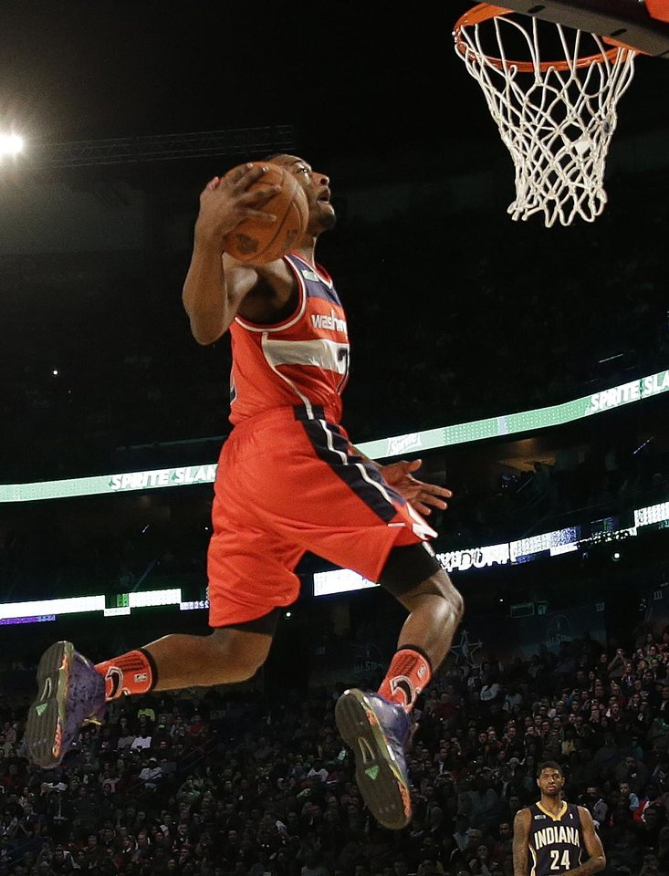 Photo - John Wall of the Washington Capitals participates in the slam dunk contest during the skills competition at the NBA All Star basketball game, Saturday, Feb. 15, 2014, in New Orleans. (AP Photo/Gerald Herbert)