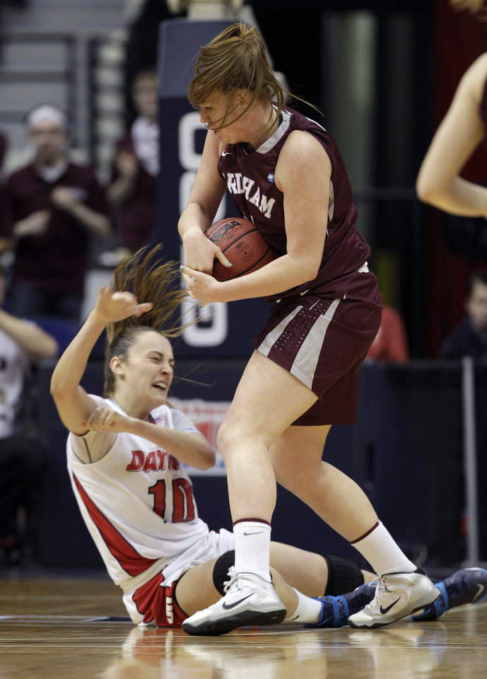 Photo - Dayton forward Andrijana Cvitkovic (10) falls to the floor in a rebound battle with Fordham forward Samantha Clark (24) during the first half of the Atlantic 10 Conference college basketball championship game in Richmond, Va., Sunday, March 9, 2014. (AP Photo/Steve Helber)