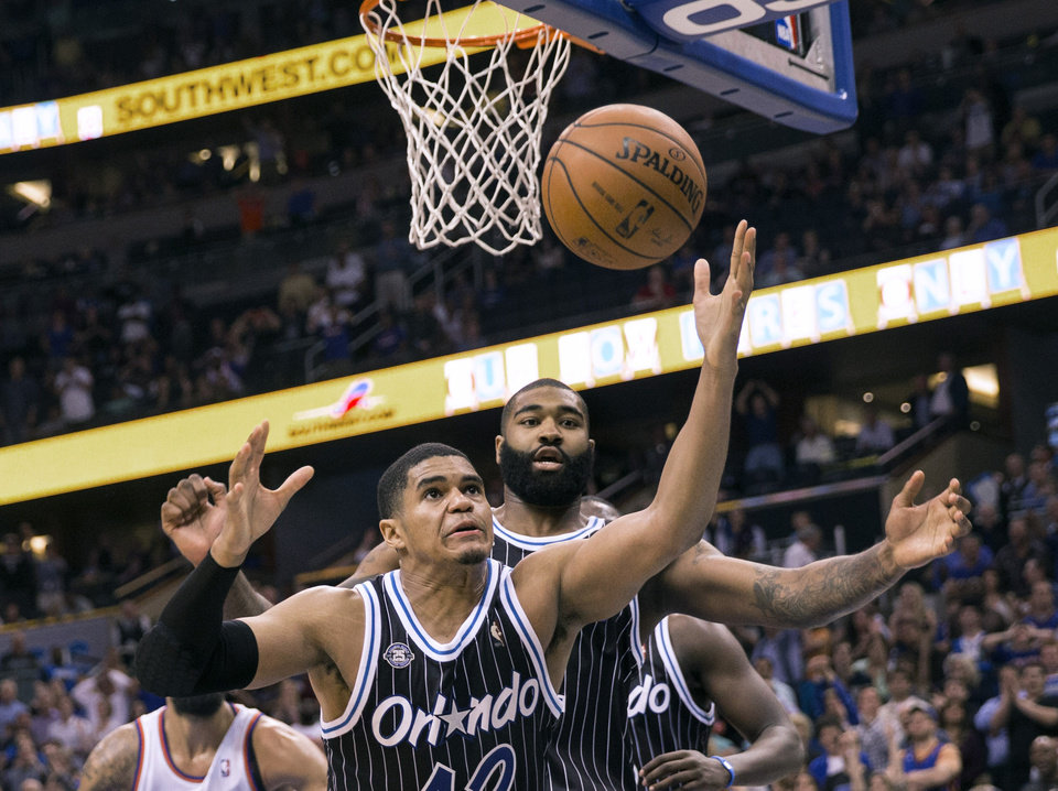 Photo - Orlando Magic's Tobias Harris (12) and Kyle O'Quinn, right, reach for a rebound after a missed New York Knicks shot in overtime of an NBA basketball game in Orlando, Fla., Friday, Feb. 21, 2014. The Magic won 129-121 in two overtimes. (AP Photo/Willie J. Allen Jr.)