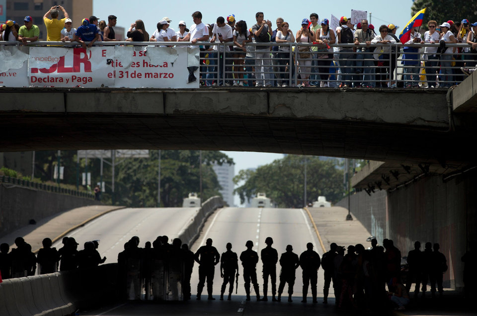 Photo - Bolivarian National Guardmen block a road to prevent demonstrators from reaching the Food Ministry, in Caracas, Venezuela, Saturday, March 8, 2014. Venezuelans returned to the streets for the
