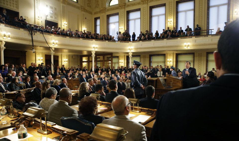 Photo - New Jersey Gov. Chris Christie, right at podium, delivers his State of the State address Tuesday, Jan. 14, 2014, at the Statehouse in Trenton, N.J. (AP Photo/Mel Evans)