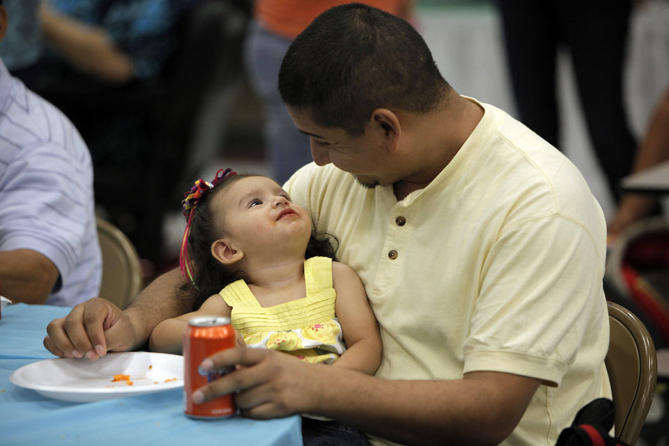 Photo - Gerardo Reyes, of Oklahoma City, finishes a meal with his daughter Belearei, 1, during a multicultural food festival at St. Eugene Catholic Church in Oklahoma City, Sunday, Sept. 9, 2012.  Photo by Garett Fisbeck, The Oklahoman  Garett Fisbeck - Garett Fisbeck