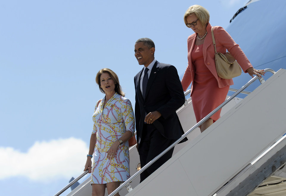 President Barack Obama, accompanied by Sen. Claire McCaskill, D-Mo., right, and Rep. Cheri Bustos, D-Ill., walks off of Air Force One at Quad Cities International Airport in Moline, Ill.,Wednesday, July 24, 2013. Obama is traveling to Knox College in Galesburg, Ill., to kick off a series of speeches that will lay out his vision for rebuilding the economy. (AP Photo/Susan Walsh)