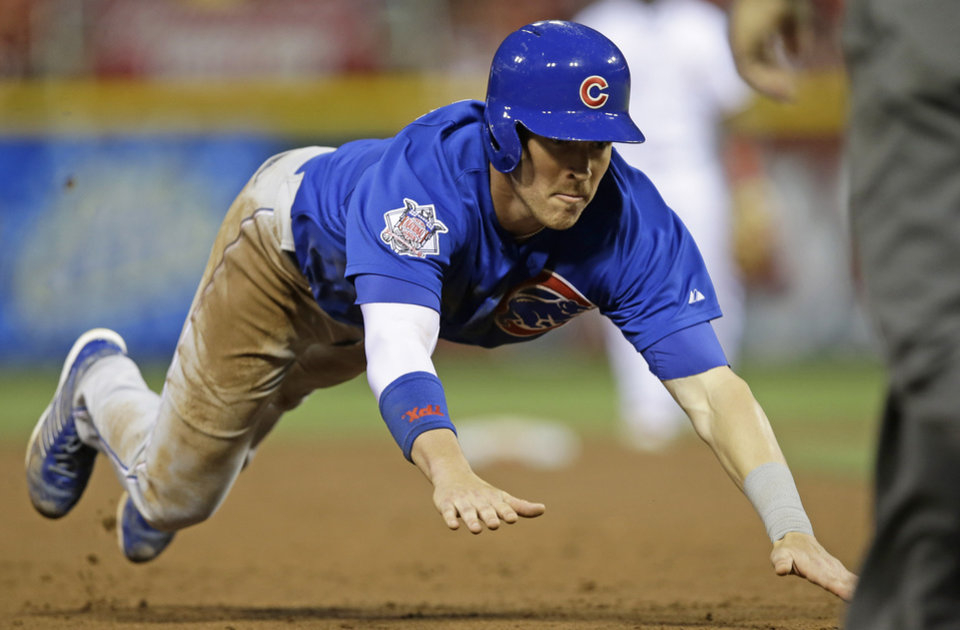 Photo - Chicago Cubs' Chris Coghlan advances safely to third base on a hit by Justin Ruggiano in the fifth inning of a baseball game against the Cincinnati Reds, Monday, July 7, 2014, in Cincinnati. (AP Photo/Al Behrman)