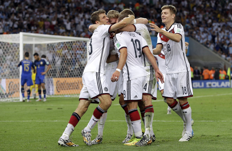 Photo - Germany's Mario Goetze, 19, is congratulated by his teammates after scoring the opening goal during the World Cup final soccer match between Germany and Argentina at the Maracana Stadium in Rio de Janeiro, Brazil, Sunday, July 13, 2014. Germany won 1-0 to win the World Cup. (AP Photo/Victor R. Caivano)