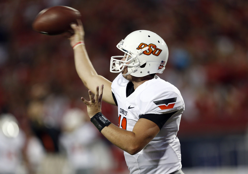 Photo - Oklahoma State's Wes Lunt (11) warms up before  the college football game between the University  of Arizona and Oklahoma State University at Arizona Stadium in Tucson, Ariz.,  Saturday, Sept. 8, 2012. Photo by Sarah Phipps, The Oklahoman