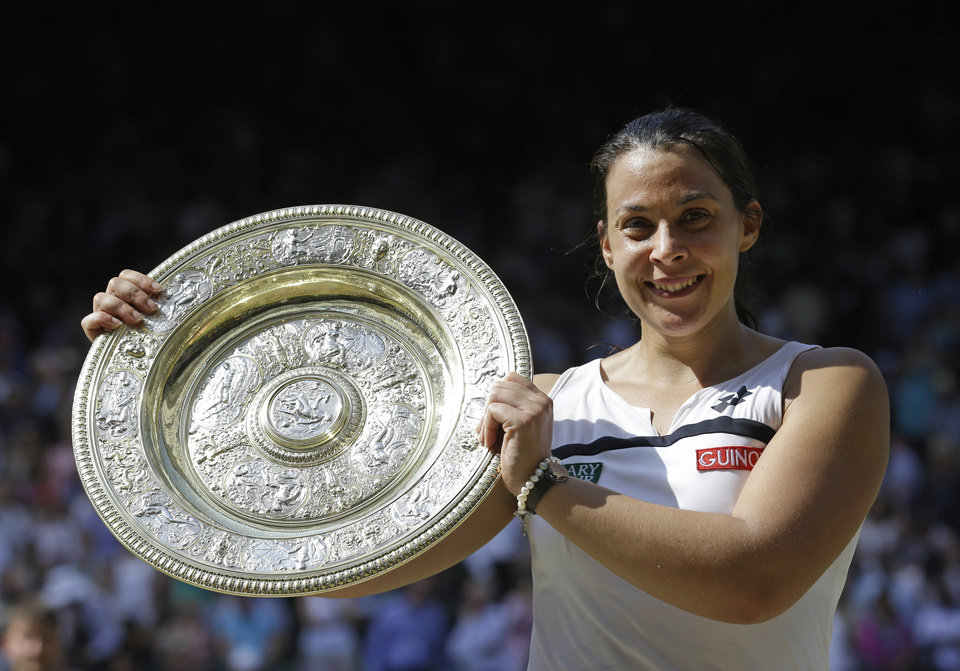 Photo - FILE - In this July 6, 2013 file photo, Marion Bartoli, of France, smiles as she holds the trophy after winning the women's singles final against Sabine Lisicki, of Germany, at the All England Lawn Tennis Championships in Wimbledon, London. Bartoli says she has no regrets about retiring shortly after winning Wimbledon a year ago. She also says she logs onto YouTube every couple of days to watch her last-point ace that ended the 2013 final at the All England Club. About six weeks after winning her only Grand Slam trophy, Bartoli announced she was quitting the sport at age 28. Bartoli is the first reigning women's champion at Wimbledon since 1997 to decline to try to defend her title. The Championships starts on June 23, 2014. (AP Photo/Anja Niedringhaus, File)