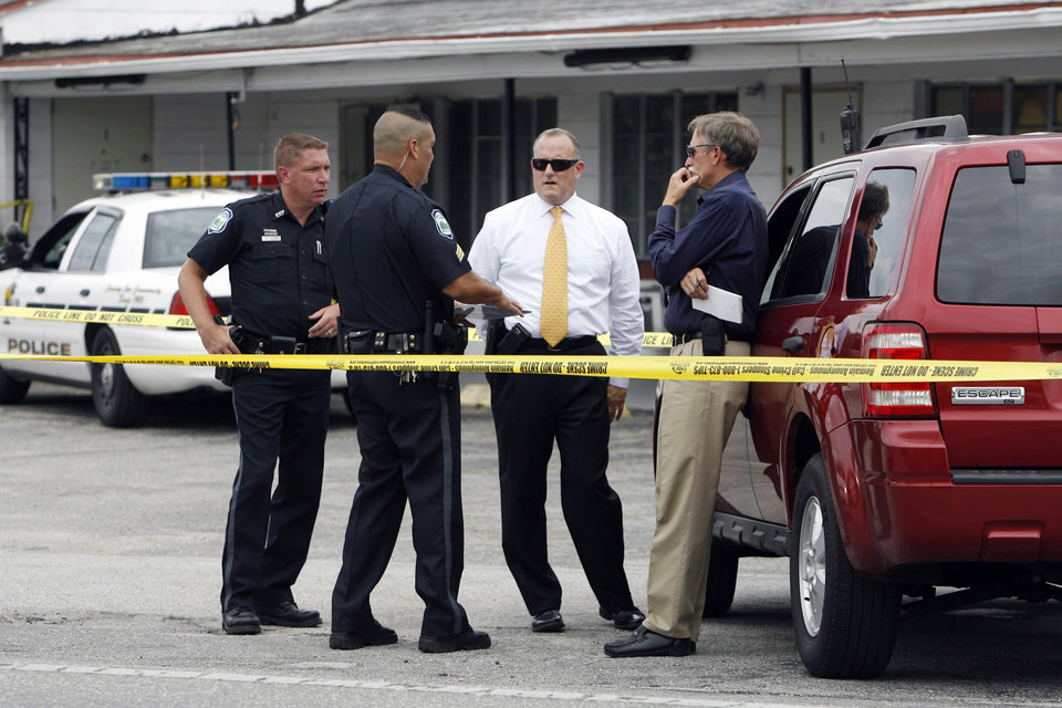 Photo -   Michael Haworth, second from right, gathers information from his officers and a detective at the scene of Kenvin's Motel, where Anthony Giancola used a microwave to attack the married couple who own the motel, Friday, June 22, 2012, in Lealman, Fla. Authorities said Giancola, an ex-Tampa Bay-area middle school principal who lost his job over a drug arrest five years ago, went on a rampage Friday, stabbing several people, killing at least two. Authorities said there were 11 victims in all, and several are being treated at area hospitals for injuries ranging from minor to life-threatening. (AP Photo/Tampa Bay Times, Melissa Lyttle) TAMPA OUT; CITRUS COUNTY OUT; PORT CHARLOTTE OUT; BROOKSVILLE HERNANDO TODAY OUT