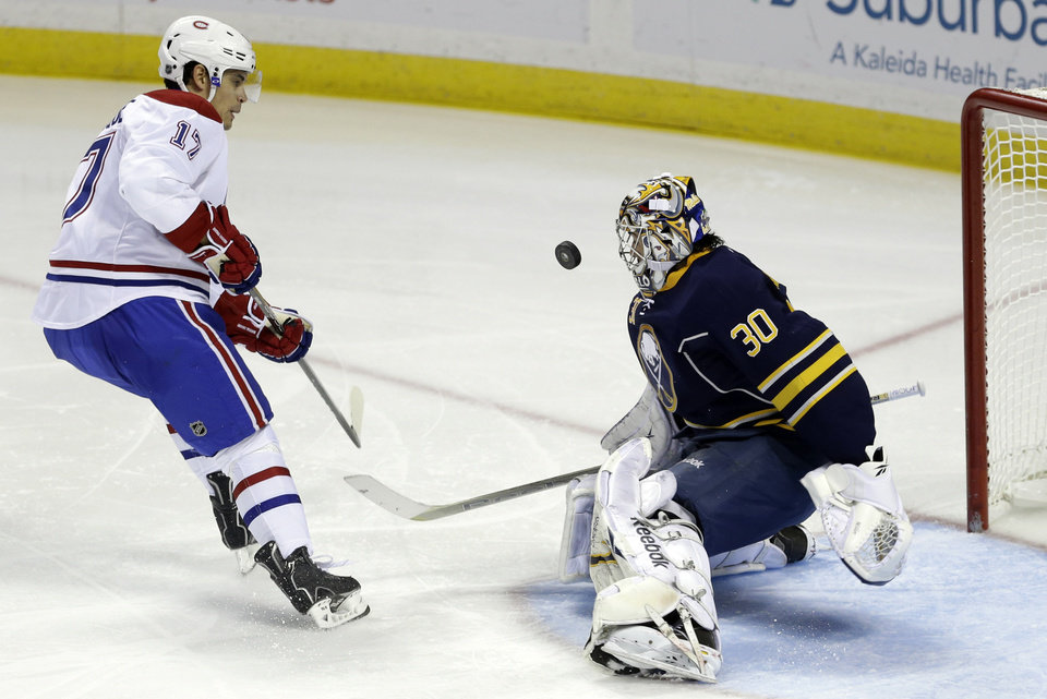 Photo - Buffalo Sabres' Ryan Miller (30) stops a shot by Montreal Canadiens' Rene Bourque (17) during the second period of an NHL hockey game in Buffalo, N.Y., Thursday, Feb. 7, 2013. (AP Photo/David Duprey)