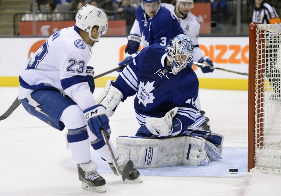 Photo - Toronto Maple Leafs goalie Jonathan Bernier, center, makes a save as Tampa Bay Lightning's J.T. Brown (23) looks for a rebound during first period of an NHL game in Toronto, Tuesday, Jan. 28, 2014. (AP Photo/The Canadian Press, Frank Gunn)