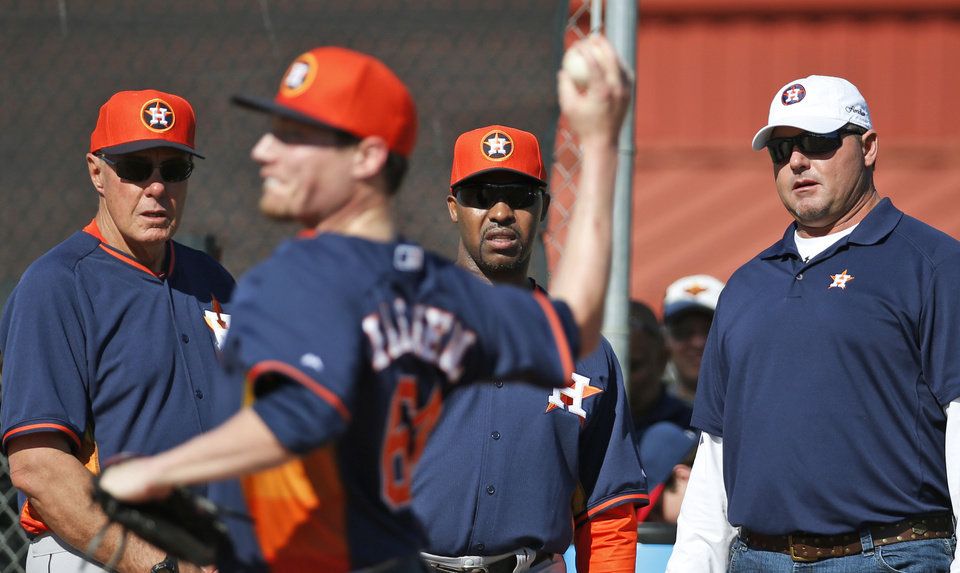 Photo - Houston Astros pitching coach Brent Strom, left, manager Bo Porter and former pitcher Roger Clemens watch as pitcher Lucas Harrell throws during baseball spring training Wednesday, Feb. 19, 2014, in Kissimmee, Fla. (AP Photo/Alex Brandon)