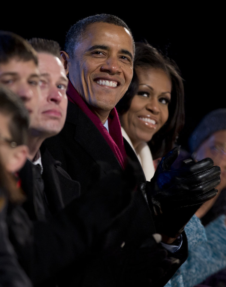 President Barack Obama and first Lady Michelle Obama look to the stage during the National Christmas Tree Lighting on the Ellipse, Thursday, Dec. 6, 2012, in Washington. This year's giant blue spruce is new, transplanted in October on the Ellipse, south of the White House.  (AP Photo/Carolyn Kaster)