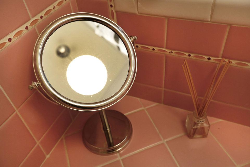 Photo - A lamp on a dressing table fits the midcentury theme of a bathroom in Mike and Lindsey Deatsch's 1949 home.  Steve Gooch - The Oklahoman
