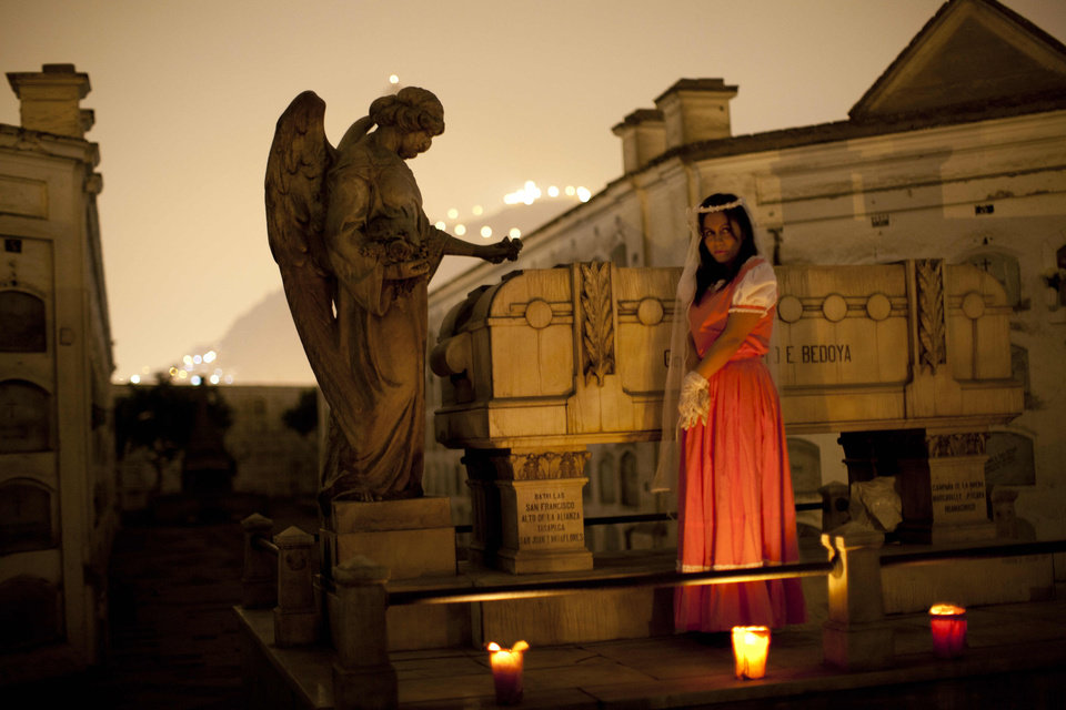 Photo - In this Sept. 20, 2012 photo, a performer dramatizes a historic event during a nighttime guided tour through the Presbitero Matias Maestro cemetery in Lima, Peru. Visitors to the 54-acre cemetery just 20 blocks from Lima's presidential palace, one of Latin America's oldest, are treated to tales about the people buried here in a three-hour, nighttime guided tour run by its owner, Beneficiencia de Lima (AP Photo/Rodrigo Abd)