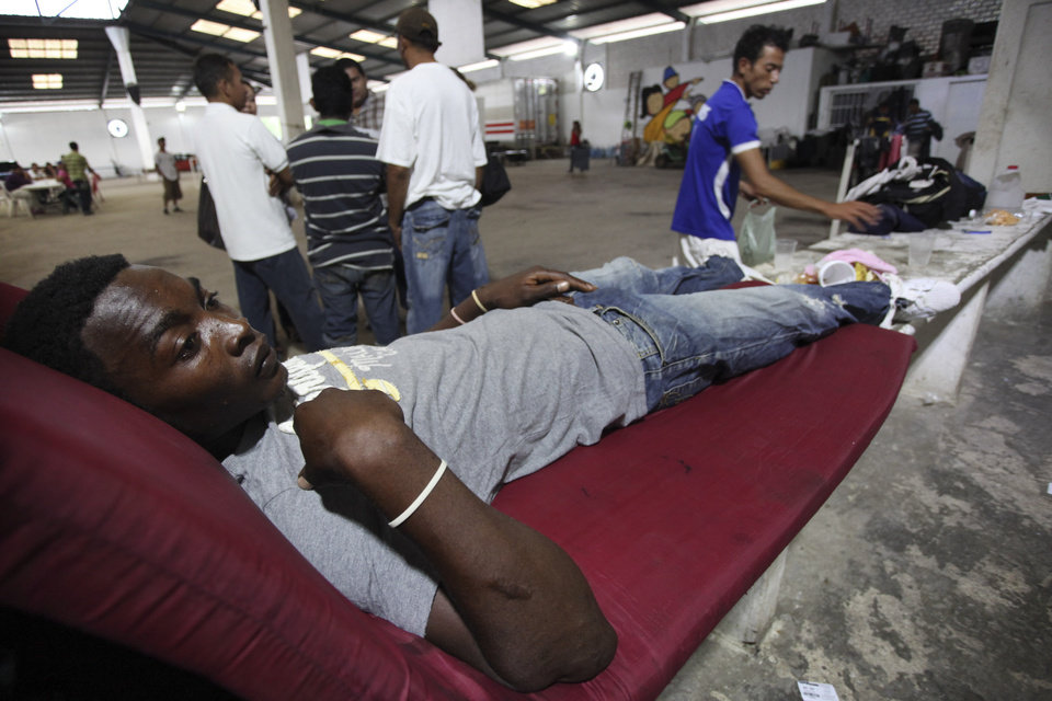Photo - Honduran migrant Wester Horbin Martinez,  23, lies in a cot after he survived a train derailment with minor injuries, at a migrant shelter in Las Choapas, southern Mexico, Sunday Aug. 25, 2013. The cargo train, known as