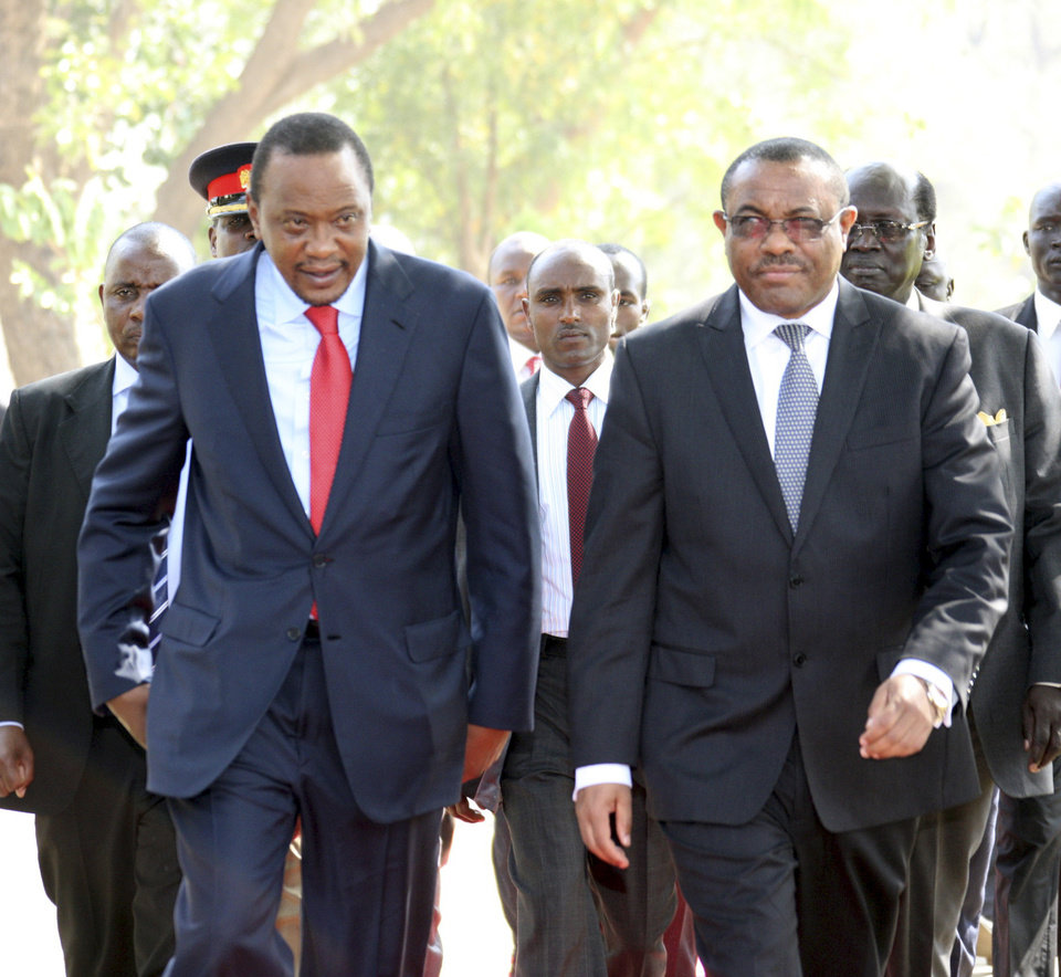 In this photo released by the Kenyan Presidential Press Service, Kenyan President Uhuru Kenyatta , left, and Ethiopian Prime Minister Hailemariam Desalegn, right, arrive for a meeting with South Sudanese President President Salva Kiir at State House in Juba, South Sudan, Thursday, Dec. 26, 2013. The leaders of Kenya and Ethiopia arrived in South Sudan on Thursday to try and mediate between the country's president and the political rivals he accuses of attempting a coup that the government insists sparked violence threatening to destroy the world's newest country.  (AP Photo/Kenyan Presidential Press Service)
