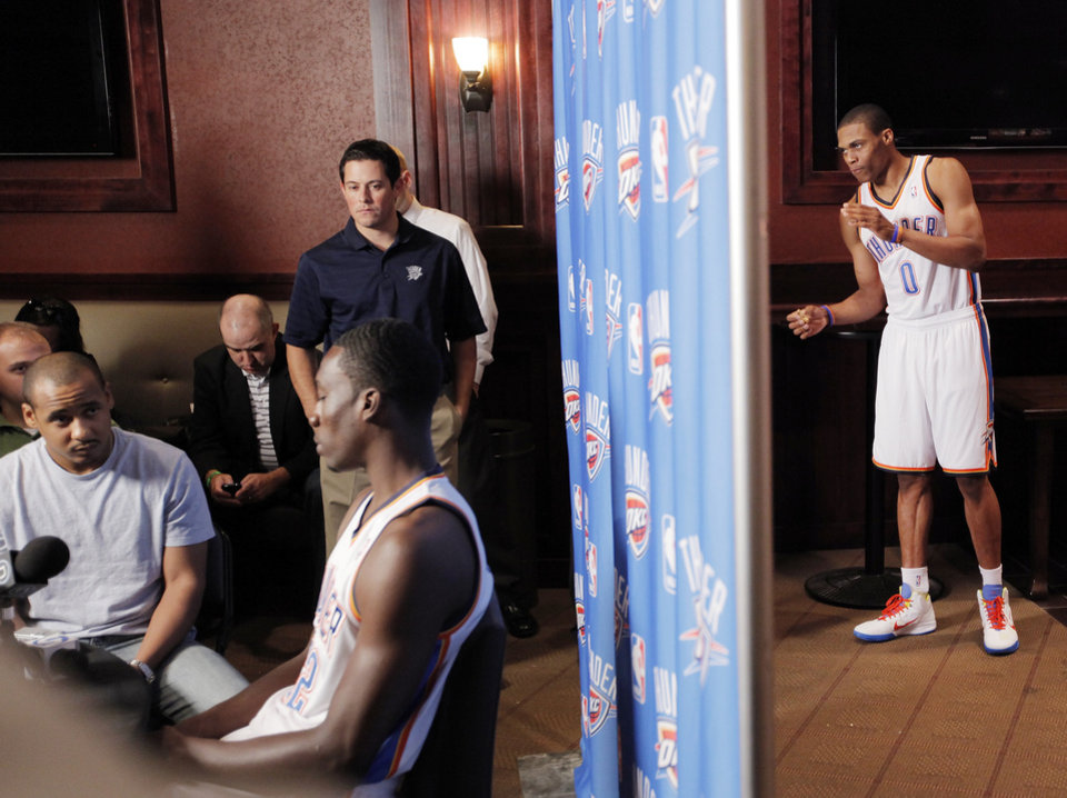 Photo - Russell Westbrook, right,  waits to talk to the media as teammate Jeff Green, left, gives an interview during media day for the Oklahoma City Thunder at the Ford Center in downtown Oklahoma City, Monday, Sept. 27, 2010. Photo by Nate Billings, The Oklahoman