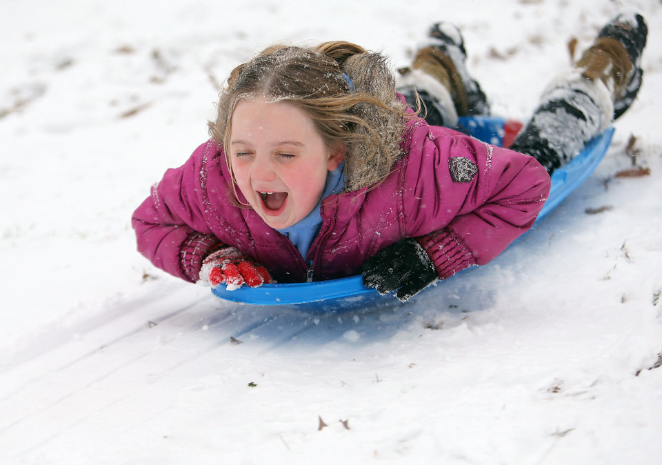 Photo - Lily Turcotte-Keen, 8, screams as she sleds down a hill at Grant Park after getting out of school early due to the snow storm on Tuesday, Jan. 28, 2014, in Atlanta. A winter storm that would probably be no big deal in the North all but paralyzed the Deep South on Tuesday, bringing snow, ice and teeth-chattering cold, with temperatures in the teens in some places. (AP Photo/Atlanta Journal-Constitution, Ben Gray)