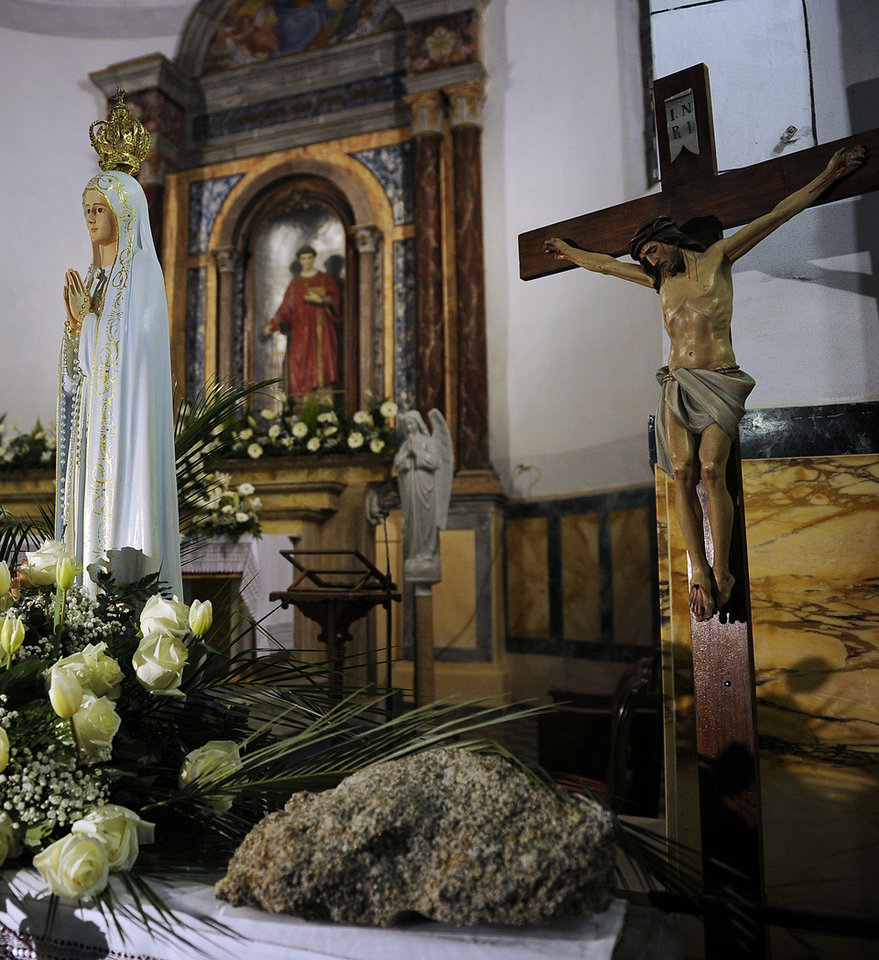 A fragment of rock which perforated the hull of the Costa Concordia cruise ship is placed near a statue of the Virgin Mary and a crucifix in a church of the Tuscan Island Isola del Giglio, Italy, Saturday, Jan. 12, 2013. More time and money will be needed to remove the Costa Concordia cruise ship from the rocks off Tuscany where it capsized last year, in part to ensure the toxic materials still trapped inside don\'t leak into the marine sanctuary when it is righted, officials said Saturday. On the eve of the first anniversary of the grounding, environmental and salvage experts gave an update on the unprecedented removal project under way, stressing the massive size of the ship — 112,000 tons, its precarious perch on the rocks off the port of Giglio island and the environmental concerns at play. (AP Photo/Gregorio Borgia)