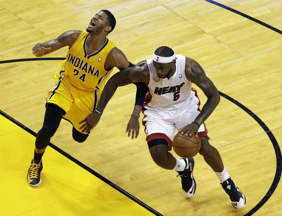 Photo - Miami Heat forward LeBron James (6) drives against Indiana Pacers forward Paul George (24) during the first half of Game 1 in their NBA basketball Eastern Conference finals playoff series, Wednesday, May 22, 2013 in Miami. (AP Photo/Wilfredo Lee)