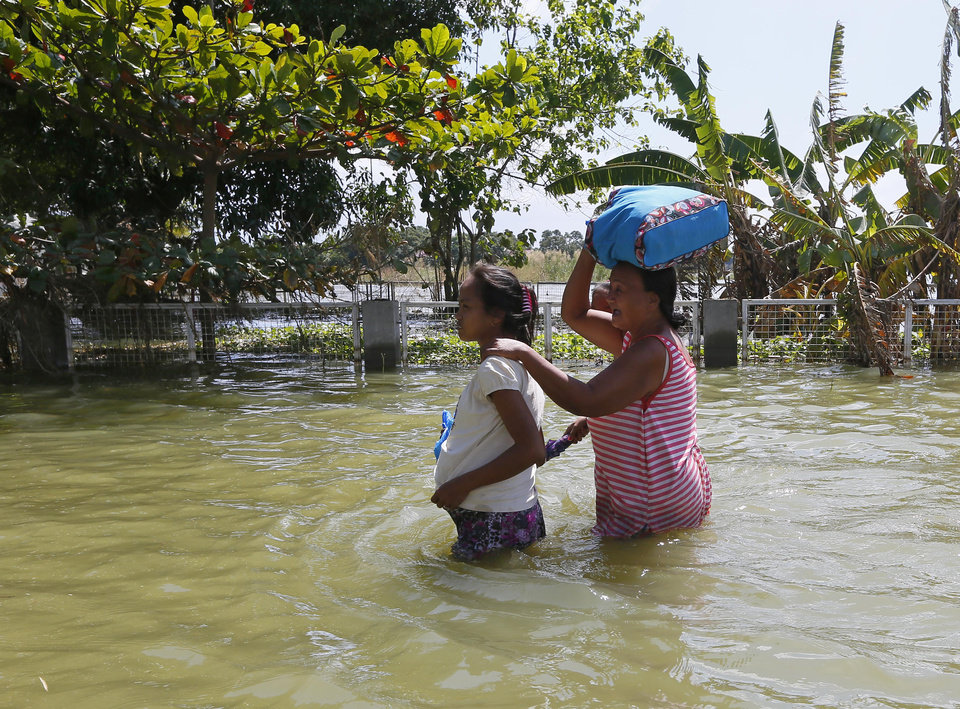 Photo - Residents wade through a flooded road which continues to be inundated by floodwaters brought about by Typhoon Koppu more than a week ago at San Simon township, Pampanga province in northern Philippines Thursday, Oct. 29, 2015. The typhoon lashed northeastern Philippines causing extensive damage to agriculture, forced thousands of residents to evacuate and killed dozens others. (AP Photo/Bullit Marquez)