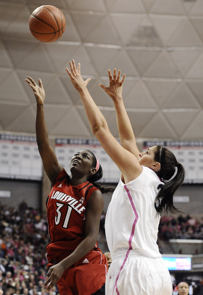 Photo - Louisville's Asia Taylor, left, shoots over Connecticut's Stefanie Dolson during the first half of an NCAA college basketball game on Sunday, Feb. 9, 2014, in Storrs, Conn. (AP Photo/Jessica Hill)