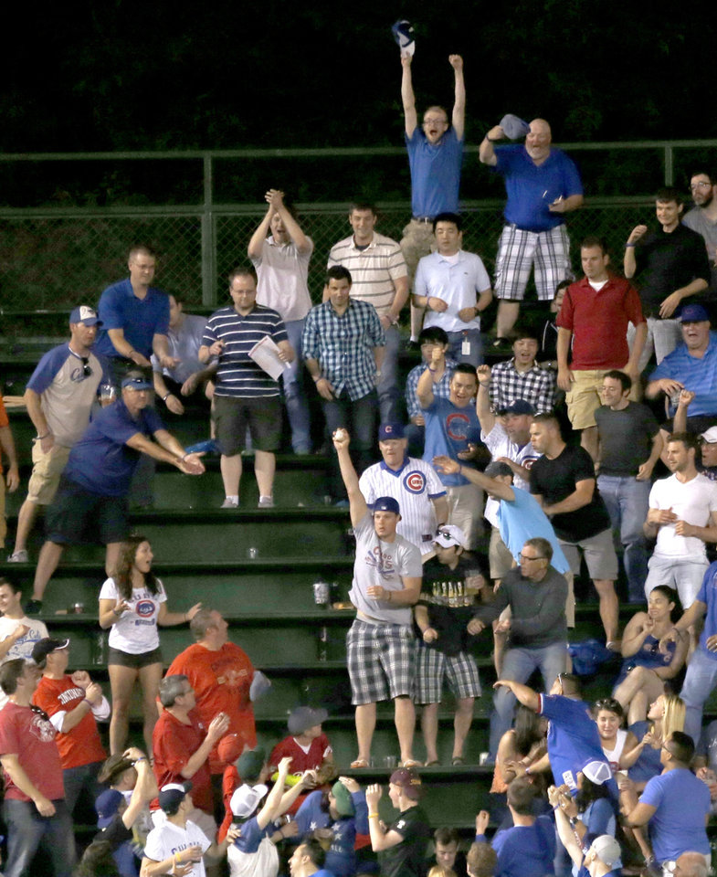 Photo - A Chicago Cubs' baseball fan catches Anthony Rizzo's home run off Cincinnati Reds starting pitcher Alfredo Simon in the left field bleachers during the sixth inning of a baseball game Monday, June 23, 2014, in Chicago. (AP Photo/Charles Rex Arbogast)