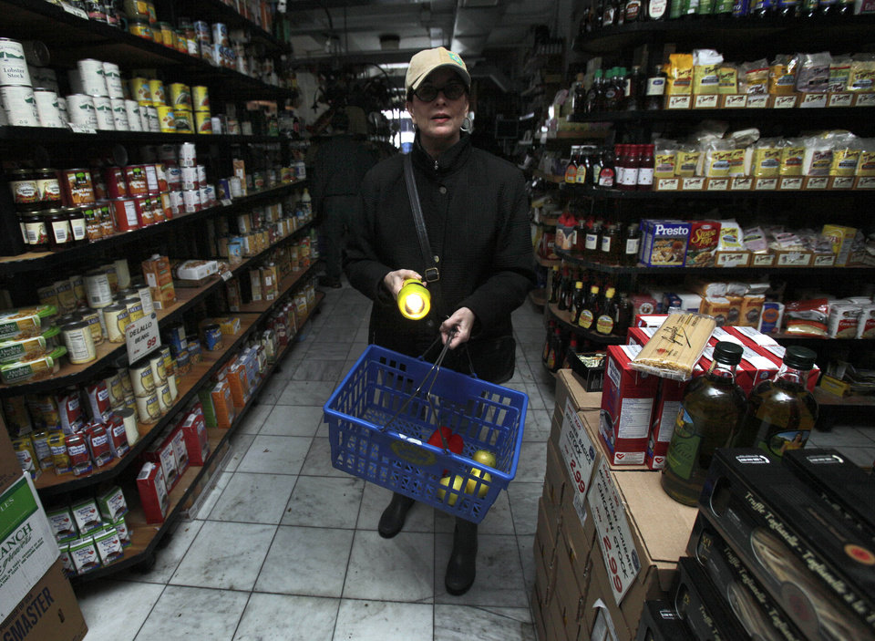 A woman shops for groceries by flashlight in the Tribeca neighborhood of New York, Tuesday, Oct. 30, 2012. ConEd cut power to some neighborhoods served by underground lines as the advancing storm surge from Hurricane Sandy threatened to flood substations. Floodwaters later led to explosions that disabled a substation in Lower Manhattan, cutting power tens of thousands of customers south of 39th Street. (AP Photo/Richard Drew) ORG XMIT: NYRD119