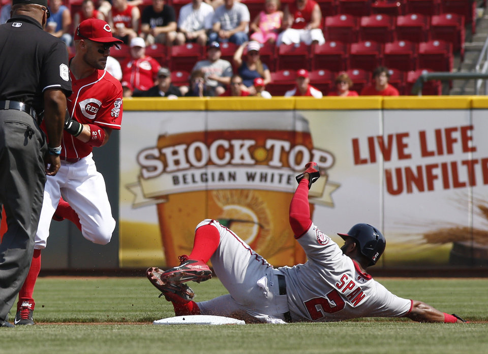 Photo - Washington Nationals' Denard Span, right, is forced out at second by Cincinnati Reds second baseman Skip Schumaker, left, after a Anthony Rendon ground ball in the first inning of a baseball game on Saturday, July 26, 2014, in Cincinnati. (AP Photo/David Kohl)