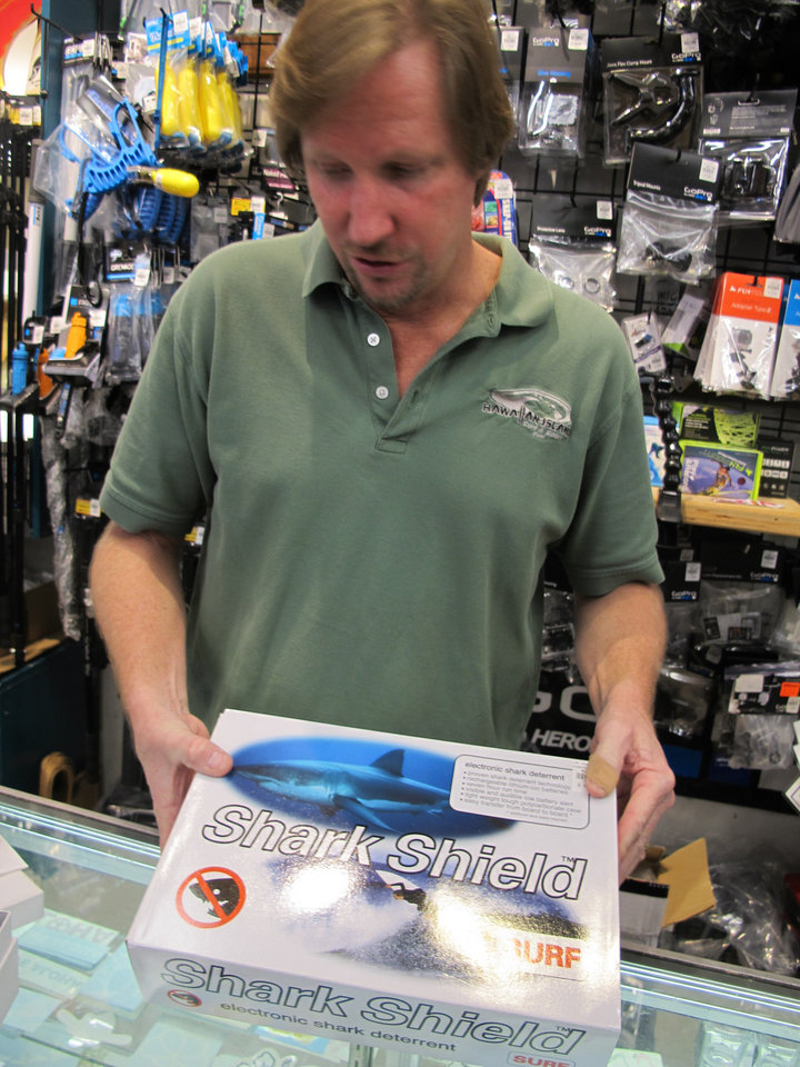 Photo - Dennis O'Donnell shows the Shark Shield shark deterrent device at his Maui store, Hawaiian Island Surf and Sport, in Kahului, Hawaii on Dec. 20, 2013. A surge in shark attacks on Maui hasn't stopped people from surfing and swimming in the warm ocean waters that surround this Hawaiian island. But it has spurred sales of devices that claim to keep sharks away by emitting an electric pulse. (AP Photo/Audrey McAvoy)