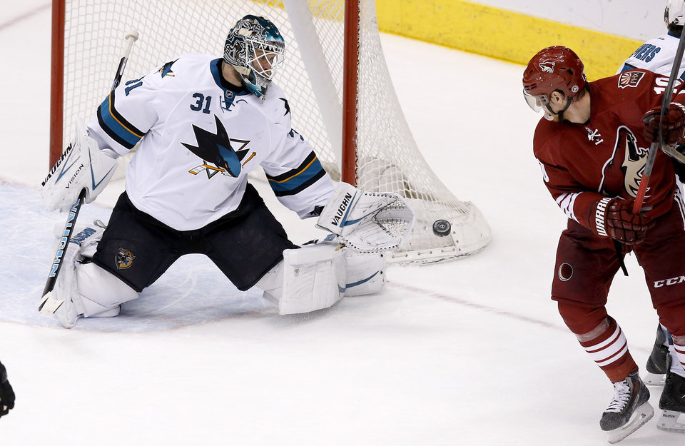 Photo - San Jose Sharks' Antti Niemi (31), of Finland, makes a save on a shot as Phoenix Coyotes' Martin Erat, right, of the Czech Republic, watches during the third period of an NHL hockey game on Saturday, April 12, 2014, in Glendale, Ariz. The Sharks defeated the Coyotes 3-2. (AP Photo/Ross D. Franklin)