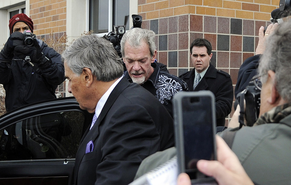Photo - Attorney James Voyles, center left, and Indianapolis Colts owner Jim Irsay, center right, leave the Hamilton County Jail in Indianapolis, Monday, March 17, 2014. Irsay was released from jail Monday after being held overnight following a traffic stop in which police said he failed sobriety tests and had multiple prescription drugs inside his vehicle. Irsay was pulled over late Sunday after he was spotted driving slowly near his home in suburban Carmel, stopping in the roadway and failing to use a turn signal. (AP Photo/Alan Petersime)