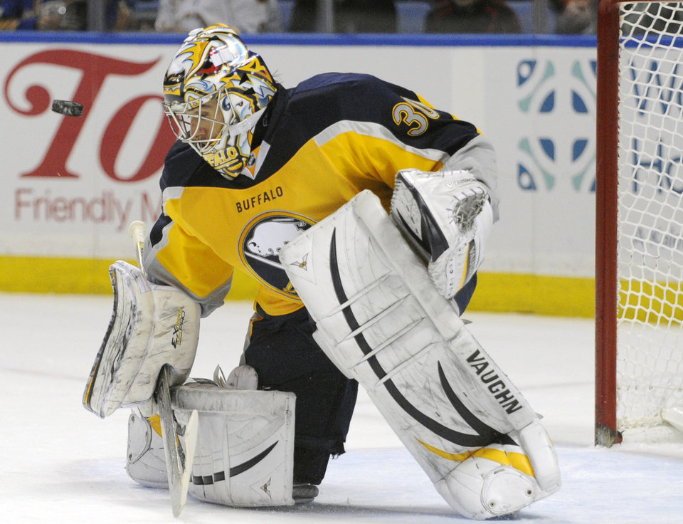Photo - Buffalo Sabres goaltender Ryan Miller has the puck bounce off his face mask during the second period of an NHL hockey game against the New Jersey Devils in Buffalo, N.Y., Saturday, Jan. 4, 2014. (AP Photo/Gary Wiepert)