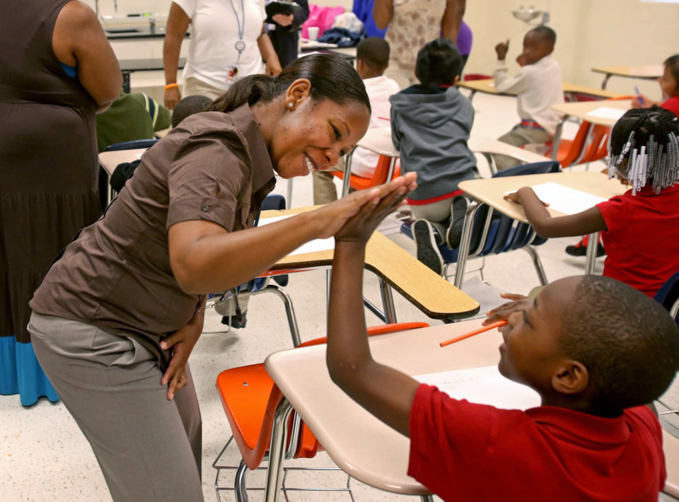 Photo - Ronald E. McNair Discovery Learning Academy first-grade teacher Danielle Pitts high-fives a student on Wednesday, Aug. 21, 2013, a day after an armed suspect caused an ordeal at their school in Decatur, Ga. The learning academy held classes at McNair High School on Wednesday after a gunman on Tuesday held one or two staff members captive and fired into the floor of the school office. As officers swarmed the campus outside, he shot at them at least a half a dozen times with an assault rifle from inside the school and they returned fire, police said. (AP Photo/Atlanta Journal-Constitution, Jason Getz)