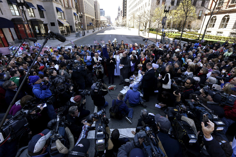 An interfaith service is held near a makeshift memorial on Boylston Street, near the finish line of the Boston Marathon, Sunday, April 21, 2013, in Boston. The city is coping in the aftermath of the marathon bombing. (AP Photo/Julio Cortez)