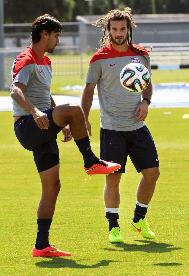 Photo - Chris Wondolowski, left, and Kyle Beckerman kick the ball around before practice starts Wednesday, June 4, 2014 in Jacksonville, Fla..  The U.S. soccer team was practicing in advance of Saturday's friendly match against Nigeria, the last before the World Cup matches in Brazil. (AP Photo/The Florida Times-Union, Bob Mack)