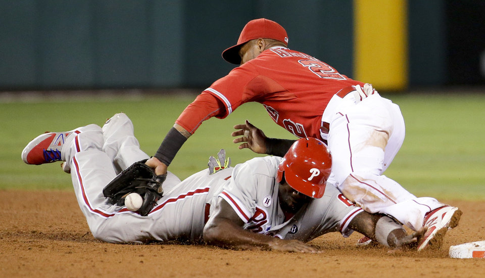 Photo - Philadelphia Phillies' Ryan Howard, bottom, dives safely back to second base after Los Angeles Angels shortstop Erick Aybar fails to catch the throw during the sixth inning of a baseball game in Anaheim, Calif., Tuesday, Aug. 12, 2014. (AP Photo/Chris Carlson)