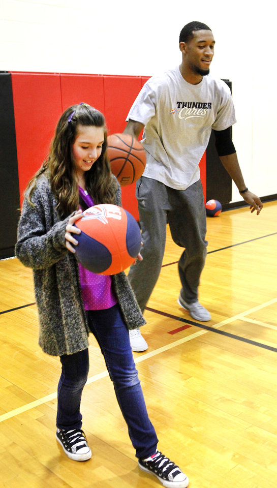 Left top: Sixth-grader Elexis Noah practices dribbling with Thunder player Perry Jones Thursday during a lesson at Cimarron Middle School in Edmond.