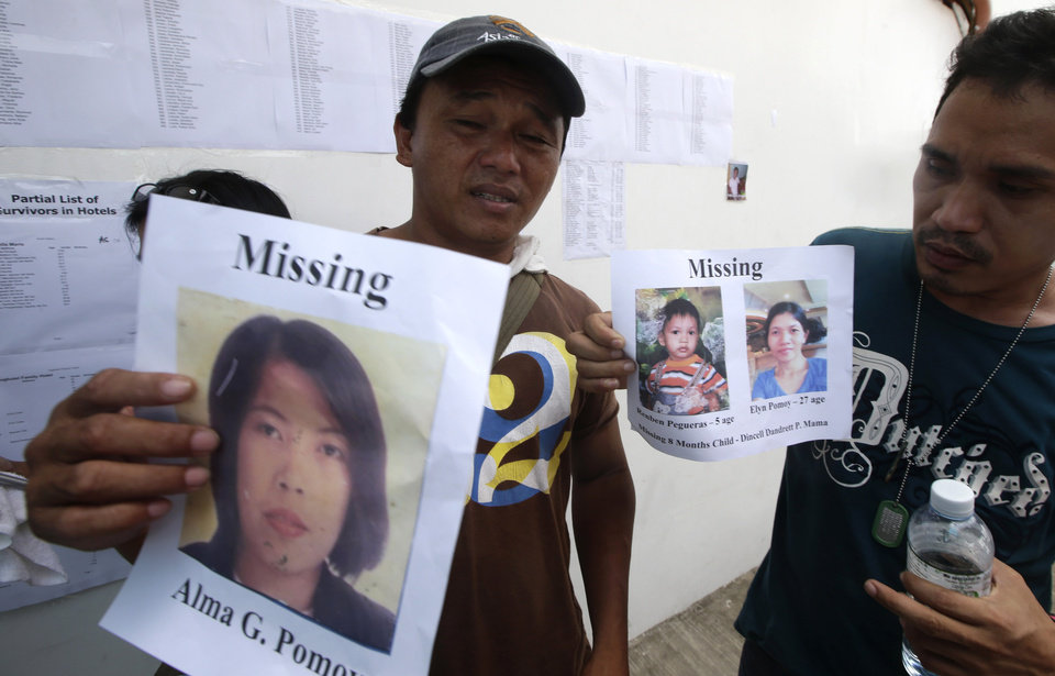 Photo - Ricky Pomoy, left, holds a print out of his missing wife Alma while Roderick Mama holds another print out of his missing wife and son outside the 2GO shipping company Sunday Aug. 18, 2013 in Cebu city, central Philippines. Divers plucked two more bodies from a sunken passenger ferry on Sunday and scrambled to plug an oil leak in the wreckage after a collision with a cargo ship. The accident near the central Philippine port of Cebu that has left 34 dead and more than 80 others missing. (AP Photo/Bullit Marquez)
